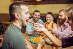 Ludzi, czasu wolnego, przyjaźni i komunikaci pojęcie, - szczęśliwi przyjaciele pije piwa, opowiadać i clinking szkła, przy barem zdjęcia royalty free