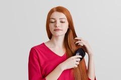 Ludzi, piękna i włosianej opieki pojęcie, Piękna piegowata kobieta długiego czerwonego włosy, czesze je, patrzeje zamyślenie pusz Fotografia Royalty Free