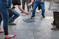 141/5000 ludzi stoi publicznie po środku ulicy oferować ich bezprawną grę piłka argelose turyści i próby, zdjęcia royalty free