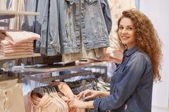 Ludzi, zakupy, stylu, mody i sprzedaży pojęcie, Szczęśliwa piękna młoda kobieta z kędzierzawym włosy, ubierającym w drelichowej k Obraz Stock
