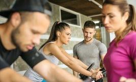 Ludzie ćwiczy na stacjonarnych rowerach w sprawności fizycznej klasie Fotografia Stock