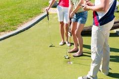 Ludzie bawić się miniaturowego golfa outdoors Zdjęcia Royalty Free
