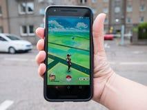 Ludzie bawić się Pokemon IŚĆ uderzenie zwiększający rzeczywistość mądrze telefon app obraz stock