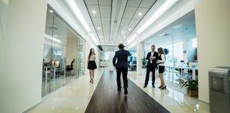 Ludzie biznesu chodzi w biurowym korytarzu, ludzie biznesu C Obrazy Royalty Free
