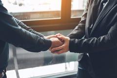Ludzie biznesu compassionately trzyma ręki przy biurowym pokojem obrazy stock
