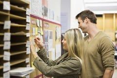 Ludzie biznesu czyta przypomnienia na tablicie informacyjnej w biurze Obraz Stock