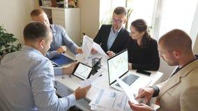 Ludzie biznesu dyskutuje dochodów wykresy i mapy podczas drużynowego spotkania w nowożytnym biurze Młodzi koledzy siedzi przy zbiory wideo