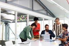 Ludzie biznesu dyskutuje nad laptopem w sali konferencyjnej zdjęcie royalty free