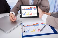 Ludzie biznesu dyskutuje wykres na cyfrowej pastylce w biurze Obraz Royalty Free