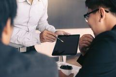 Ludzie biznesu egzamininuje pieniężnych raporty i analizuje biznesowego przyrosta w pastylka ekranie obraz stock