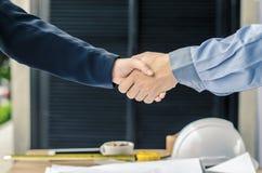 ludzie biznesu handshaking przy tłem nad hełmami, dokumenty, pracownika narzędzie Zdjęcia Stock