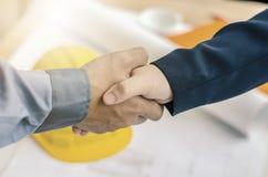 ludzie biznesu handshaking przy tłem nad hełmami, dokumenty, pracownika narzędzie Obrazy Stock