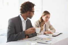 Ludzie biznesu ma kawową patrzeje gazetę Zdjęcia Stock