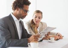 Ludzie biznesu ma kawową patrzeje gazetę Obrazy Stock