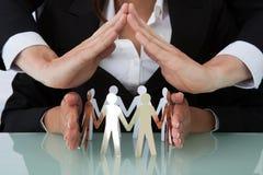 Ludzie biznesu osłania drużyny papierowi ludzie przy biurkiem Zdjęcie Stock