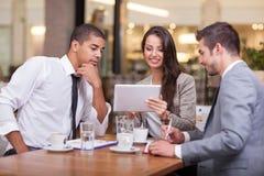 Ludzie biznesu patrzeje cyfrową pastylkę w cafffee podczas ja Fotografia Royalty Free