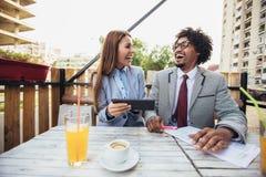 Ludzie biznesu patrzeje cyfrow? pastylk? i dyskutuj? o przysz?o?ciowym projekta planie w kawiarni zdjęcie royalty free