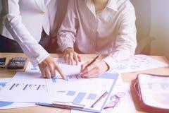 Ludzie biznesu planują ich pracę i wskazują wykresy na dobre pracę zespołową Obrazy Stock