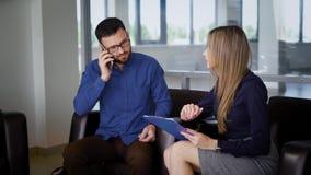 Ludzie biznesu pracują wpólnie w nowożytnym budynku biurowym z okno w tle Mężczyzna mówi dalej zbiory wideo