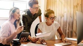 Ludzie biznesu pracuje wpólnie na projekcie przy początkowym biurem zdjęcia royalty free