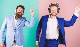 Ludzie biznesu słucha muzykę z hełmofonami Koledzy słuchają muzyka muzyka relaksuje Mężczyzna brodate twarze formalne obrazy royalty free