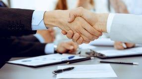 Ludzie biznesu trząść ręki przy spotkaniem podczas gdy ich koledzy klascze i oklaskuje Grupa niewiadomi biznesmeni zdjęcie stock