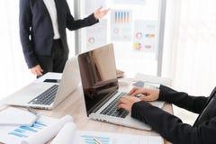 Ludzie biznesu używa laptop i Pieniężne mapy przy spotkaniem Fotografia Royalty Free
