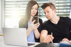 Ludzie Biznesu Używa Mądrze telefon Przy biurkiem W biurze Obrazy Stock