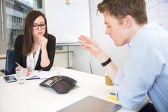 Ludzie Biznesu Używa Konferencyjnego telefon Przy spotkania biurkiem Fotografia Stock
