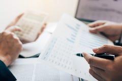 Ludzie biznesu wskazuje na statystyki liczby rezultacie i analiza finanse kosztujących z sprawdzać zbiorczych raportów wykres w b zdjęcia royalty free