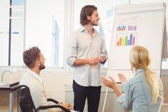 Ludzie biznesu z męskim kolegą patrzeje wielo- barwionego wykres Obrazy Royalty Free