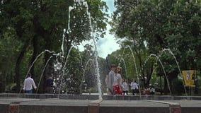 Ludzie blisko fontanny w Kij?w w Shevchenko parku na wiosna dniu zbiory wideo