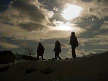 Ludzie chodzą na śniegu na wzgórzu pod słońca światłem Zdjęcie Stock