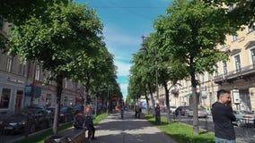 Ludzie chodzą na zielonej alei w lato słonecznym dniu w mieście architektura ławka zbiory