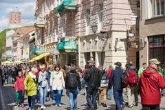 Ludzie chodzą ulicą stary miasteczko z Gediminas wierza przy tłem w Vilnius, Lithuania Obrazy Stock