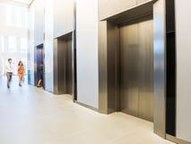 Ludzie chodzą w biurze za windami, Nowożytny stalowy elevat Zdjęcie Stock