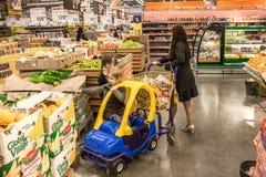 Ludzie chodzą wokoło centrum handlowego i kupują towary karmowych i codziennych Sklepowi sprzedawanie produkty Ludzie z wózek na  zdjęcia royalty free