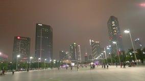 Ludzie chodzą wzdłuż nocy ulicznego guacnzhou, drapacz chmur w tle Wielka zwyczajna ulica w Guangzhou zbiory wideo