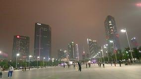 Ludzie chodzą wzdłuż nocy ulicznego guacnzhou, drapacz chmur w tle Wielka zwyczajna ulica w Guangzhou zdjęcie wideo