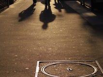 Ludzie chodzącego cienia ciskającego na ulicie Zdjęcia Royalty Free