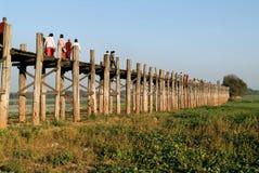 Ludzie chodzi na drewnianym moscie U Bein na rzecznym Ayeyarwad Obraz Stock