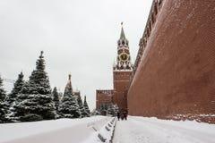 Ludzie chodzi obok Kremlin Spasskaya i ściany górują w zimie Fotografia Stock