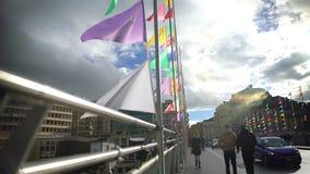 Ludzie chodzi przez most dekorującego z barwionymi flaga, wakacyjna atmosfera zbiory wideo