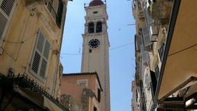 Ludzie chodzi przez starej grodzkiej części Corfu grodzki Grecja z swój małymi sklepami jerzyki lata wokoło Dzwonkowy wierza St zbiory