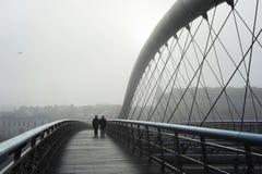 Ludzie chodzi przy Krakow ojca Bernatek footbridge w mgłowym weaher, pejzaż miejski w tle zdjęcie royalty free