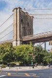 Ludzie chodzi w ulicach blisko mostu brooklyńskiego parka z mostem brooklyńskim nad drzewami, obrazy royalty free