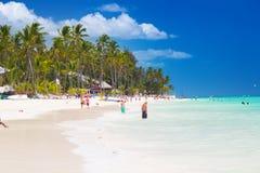 Ludzie chodzi wzdłuż linii brzegowej i sunbathing na jeden najlepszy plaża w Karaibskim terenie Fotografia Royalty Free