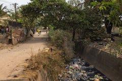 Ludzie chodzi wzdłuż na wolnym powietrzu kanału ściekowego przy Bandim Neighbourhood jeżeli miasto Bissau zdjęcia royalty free