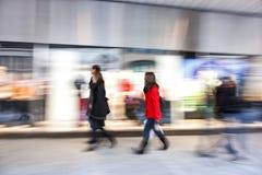 Ludzie chodzi za sklepu okno, zoomu skutek, ruch plama Obraz Royalty Free