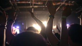 Ludzie ciągną ręki up przy rockowym koncertem, zwolnione tempo zdjęcie wideo